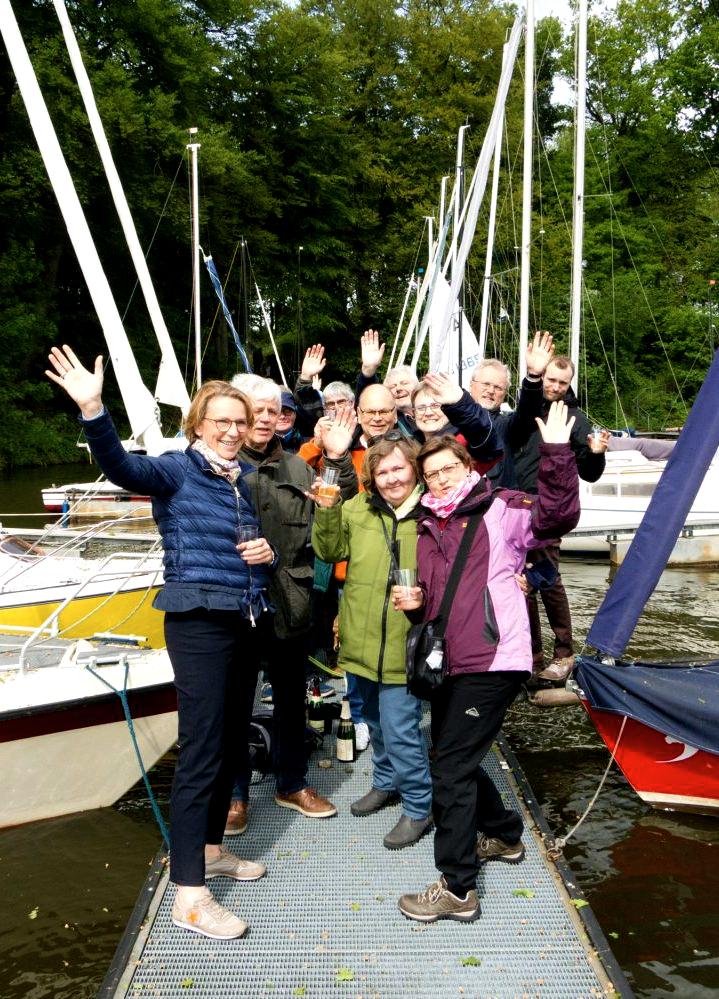 Vereinsmitglieder des Segelclub Marl e.V. stehen auf dem Steg un winken